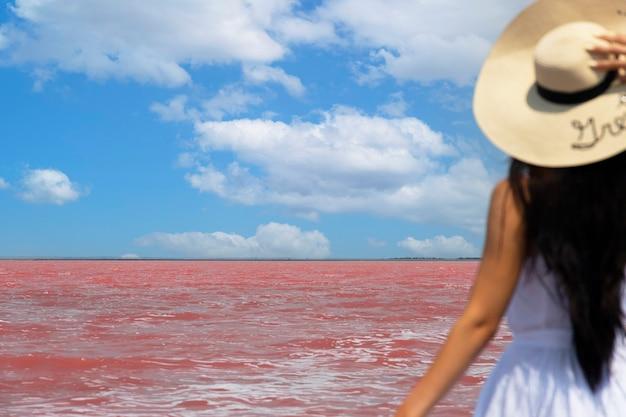 Frauenreisender mit hut betrachtet erstaunlichen exotischen rosa salzsee und blauen himmel. reisekonzept fernweh, platz für text kopieren. selektiver fokus. foto in hoher qualität