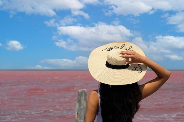 Frauenreisender mit hut betrachtet erstaunlichen exotischen rosa salzsee und blauen himmel. reisekonzept fernweh, platz für text kopieren