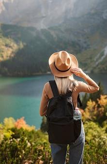 Frauenreisender mit hut und blick auf erstaunliche berge und see, fernweh-reisekonzept. see morskoy eye in der polnischen tatra.