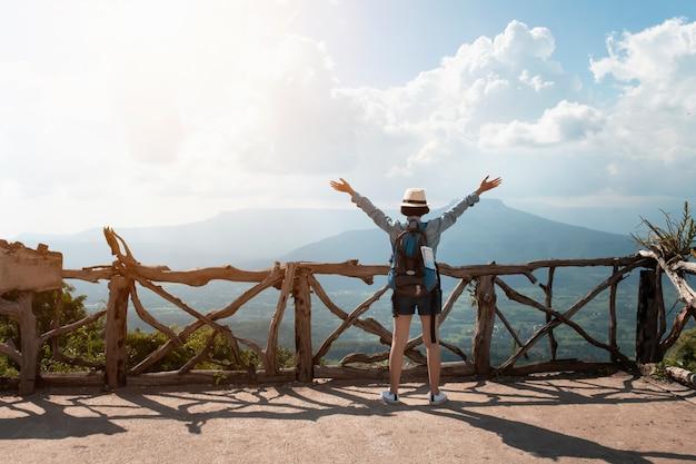 Frauenreisender mit rucksack ansicht und glückliche freiheit an den bergen genießend