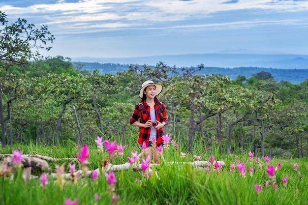 Frauenreisender mit rucksack, der am krachiew-blumenfeld, thailand genießt. reisekonzept.