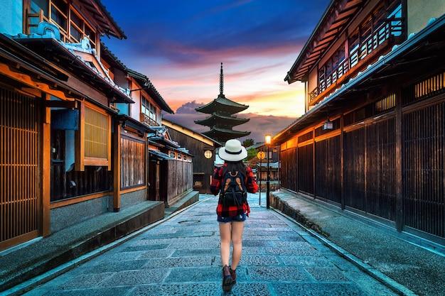 Frauenreisender mit rucksack, der an yasaka-pagode und sannen-zaka-straße in kyoto, japan geht.