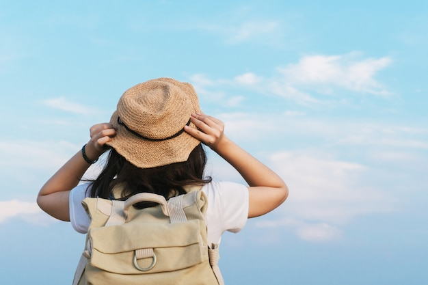 Frauenreisender mit rucksack, der hut hält und den blauen himmel, reisekonzept, raum für text und atmosphärischen moment betrachtet