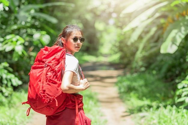 Frauenreisender mit rucksack im wald
