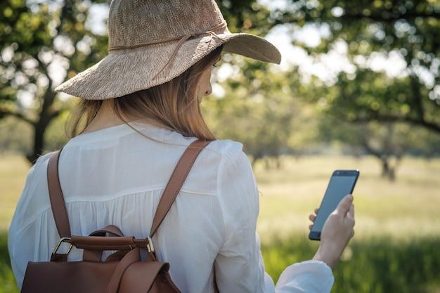 Frauenreisender mit rucksack und hut, die im erstaunlichen wald, fernweh-reisekonzept, atmosphärischen moment gehen. tag der erde. verwenden sie das smartphone, um den weg zu finden, karte