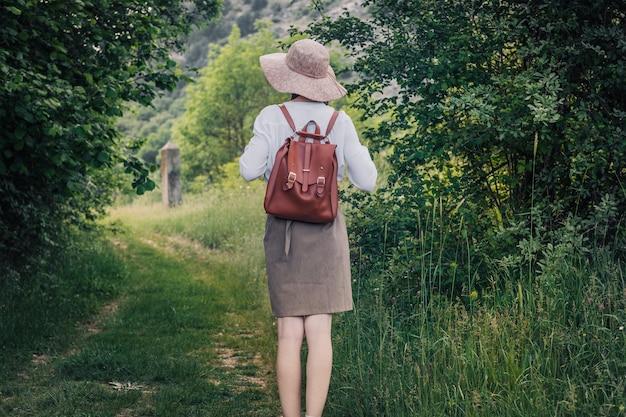 Frauenreisender mit rucksack und hut, die in erstaunlichen bergen und im wald gehen, fernweh-reisekonzept, raum für text, atmosphärischen moment. tag der erde