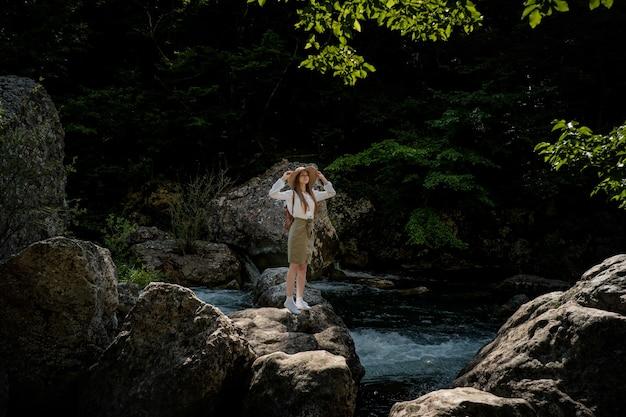 Frauenreisender mit rucksack und hut, die in erstaunlichen bergen und wald nahe fluss mit tiefblauem wasser gehen