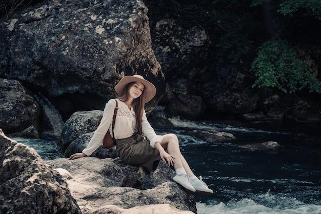 Frauenreisender mit rucksack und hut, die in erstaunlichen bergen und wald nahe fluss mit tiefblauem wasser gehen Premium Fotos