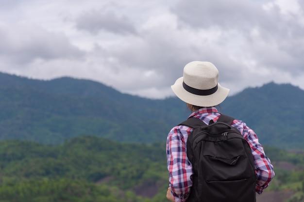 Frauenreisender mit rucksacktourist am berg