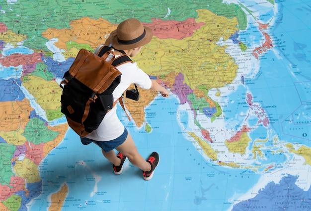 Frauenreisender plant eine tour, die sie auf der weltkarte steht. sie zeigt auf die karte