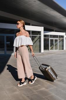 Frauenreisender tourist, der mit gepäck am bahnhof aktiv und reiselebensstilkonzept geht