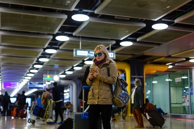 Frauenreisendtourist, der mit gepäck an der bahnstation geht. aktiv und reise lifestyle-konzept
