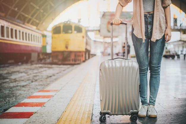 Frauenreisentourist, der mit gepäck an der bahnstation steht