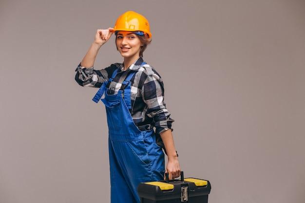 Frauenreparaturbetrieb in der uniform mit werkzeugkasten