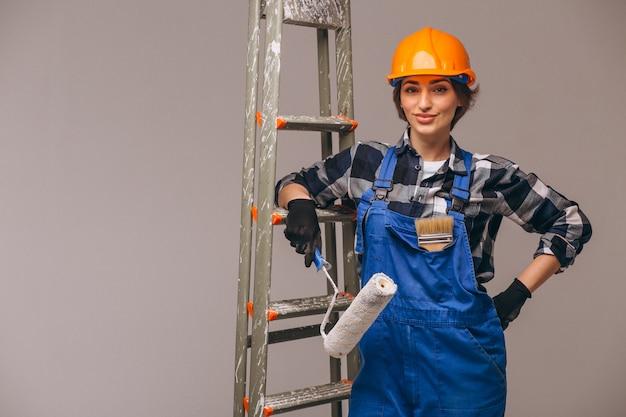 Frauenreparaturmeister mit strichleiter in einer uniform lokalisiert
