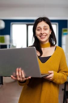 Frauenretusche, die lächelnd in die kamera schaut und in einer kreativen medienagentur arbeitet, die in einer multimediafirma mit laptop steht