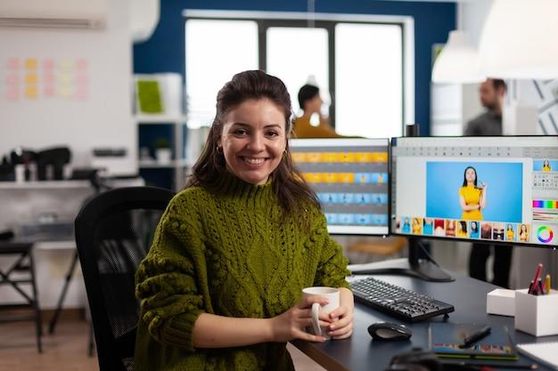 Frauenretusche, die lächelnd in die kamera schaut und in einer kreativen medienagentur sitzt und kundenfotos auf dem pc mit zwei displays retuschiert