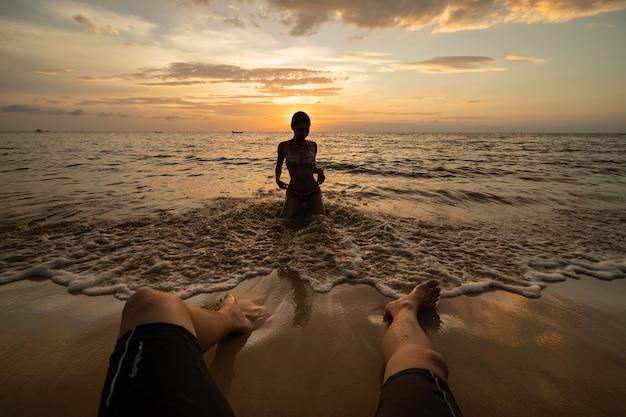 Frauenschattenbild am strand bei sonnenuntergang mit mannbeinen