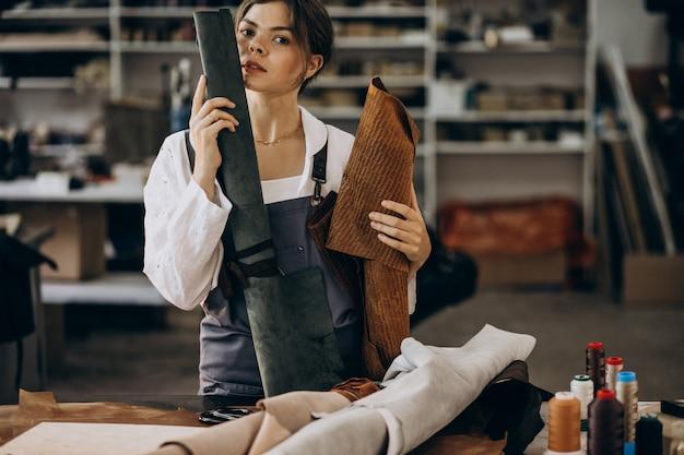 Frauenschneider, der an lederstoff arbeitet