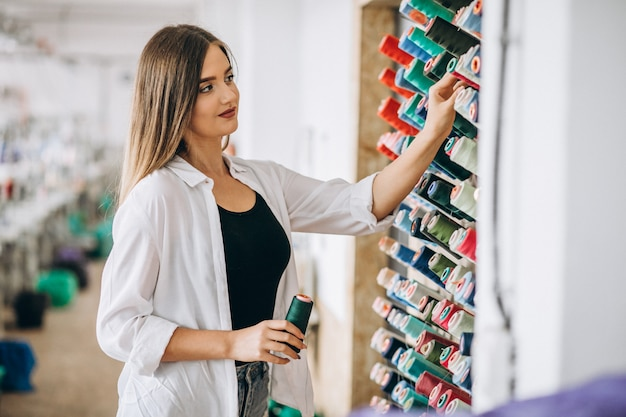 Frauenschneider, der threads an einer fabrik wählt