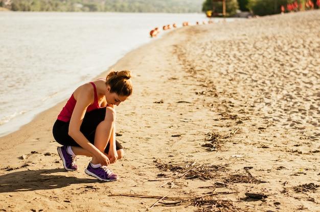 Frauenschnürensportschuhe und werden fertig zum laufen und trainieren am strand auf sommer