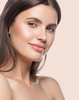 Frauenschönheitsgesicht gesunde saubere haut natürliche make-upschönheit mustert weibliches junges modell beige hintergrund.
