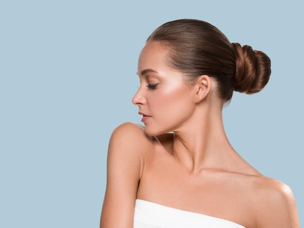 Frauenschönheitsgesicht gesundes haut natürliches make-up schönes junges modell. farbiger hintergrund. blau