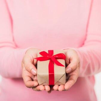 Frauenschönheitshände, die kleine geschenkverpackungsbox halten, verpacktes papier mit band