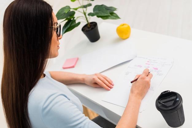 Frauenschreiben auf den papieren, die am tisch sitzen