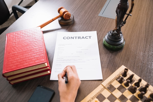 Frauenschreiben im dokument bei tisch mit büchern, smartphone, schach und hammer