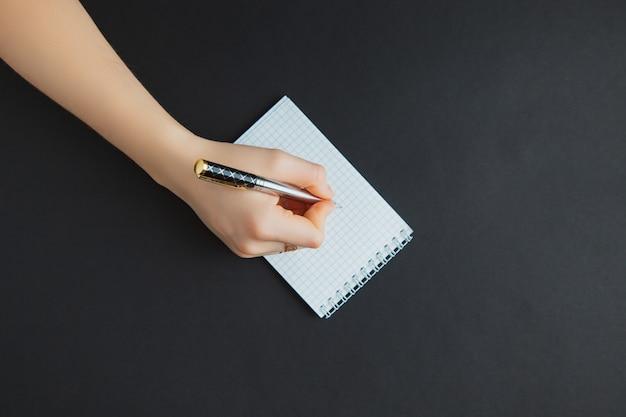 Frauenschreiben im notizblock am schwarzen tisch