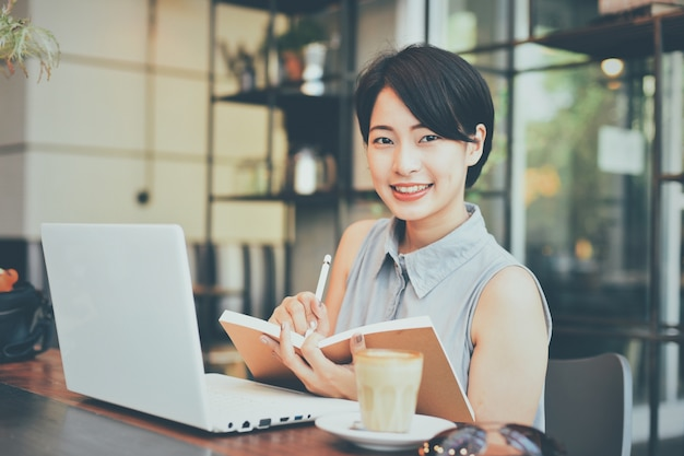 Frauenschreiben in einem notizbuch in einem café