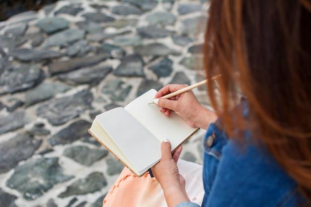 Frauenschreiben in ihrem persönlichen tagebuch, draußen.