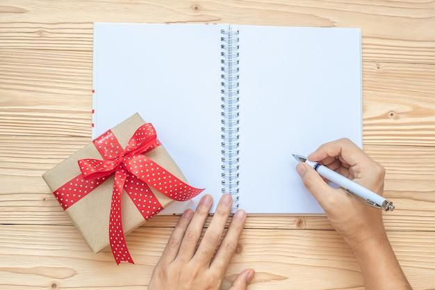 Frauenschreiben mit notizbuch und weihnachtsdekoration auf holztisch