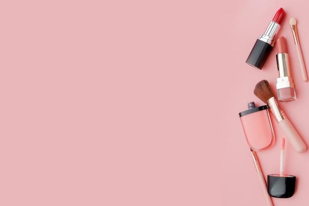 Frauenschreibtisch mit dekorativer kosmetik für make-up auf rosa hintergrund flach legen platz für text
