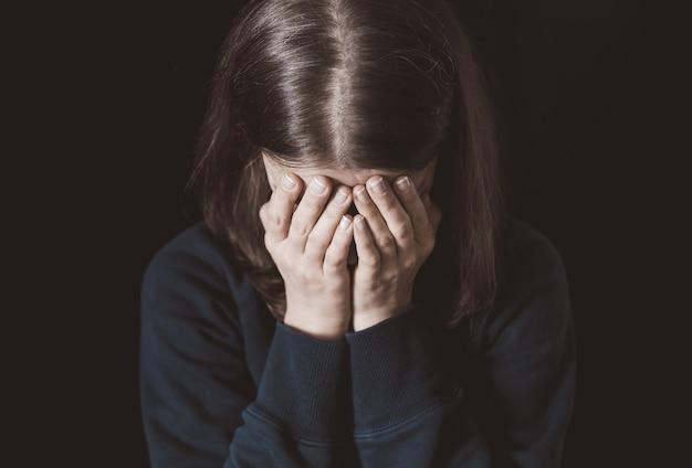 Frauenschreie, die ihr gesicht mit ihrer hand auf einem schwarzen hintergrund bedecken