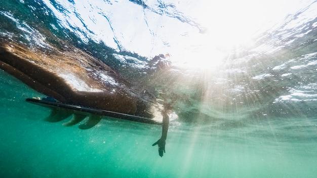 Frauenschwimmen auf surfbrett im blauen ozean
