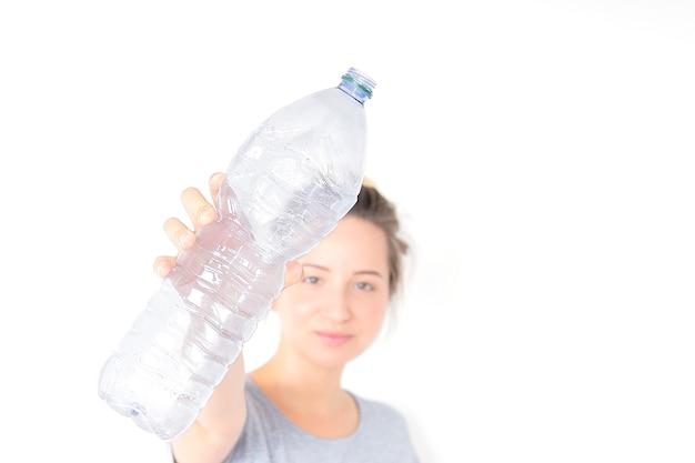 Frauenshows und halten der recyclebaren plastikflasche lokalisiert auf weißem hintergrund.