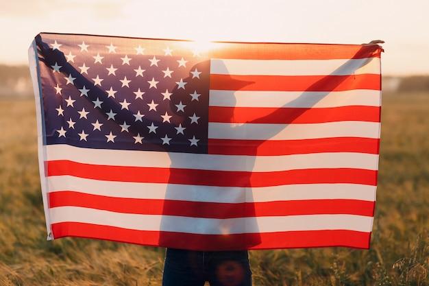Frauensilhouette im landwirtschaftlichen feld jenseits der usa-flagge auf sonnenuntergang