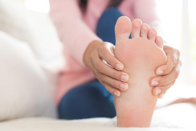 Frauensitzen und hält ihre fußverletzung und fühlt schmerz. gesundheits-konzept.