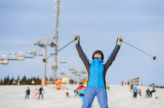 Frauenskifahrer, der abwärts am skiort gegen skilift ski fährt