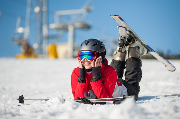 Frauenskifahrer, der mit skis auf schneebedecktem an der gebirgsspitze liegt
