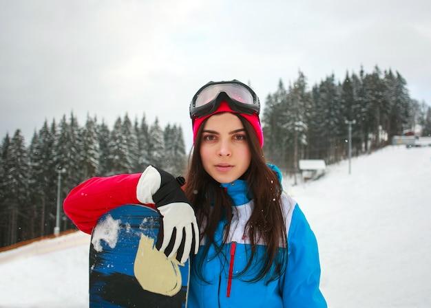 Frauensnowboarder im winter am skiort auf hintergrund von kiefern