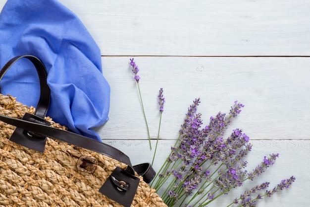 Frauensommertasche mit lavendelblumen und blauem schal auf pastellfarbhölzernem hintergrund