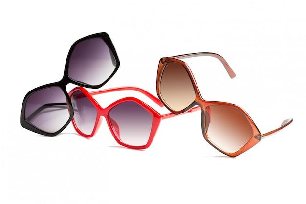 Frauensonnenbrille, die in verschiedenen farben lokalisiert auf weiß spielt