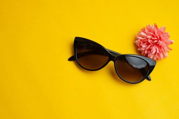 Frauensonnenbrille mit blume auf gelb. sommerferien-konzept.