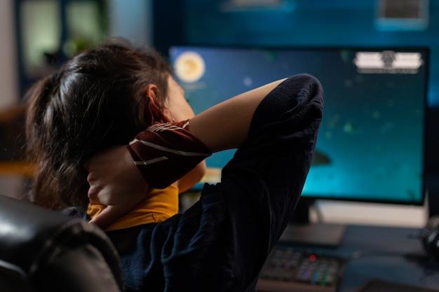 Frauenspielerin, die den hals ausstreckt, bevor sie online-videospiele auf einem leistungsstarken computer im gaming-studio spielt. aufgeregter spieler, der auf einem gaming-stuhl sitzt und videospiele mit dem rgb-schlüsselwort streamt