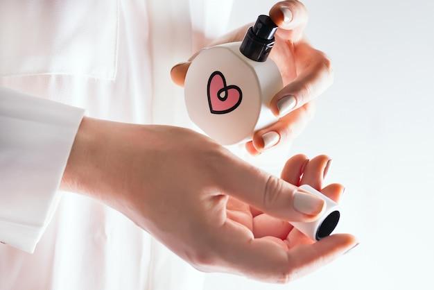 Frauensprühparfüm auf ihrem handgelenk. hände und parfümflasche im fokus.