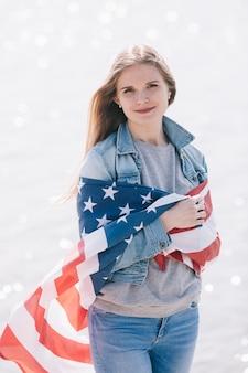 Frauenstellung eingewickelt in der amerikanischen flagge und im betrachten der kamera