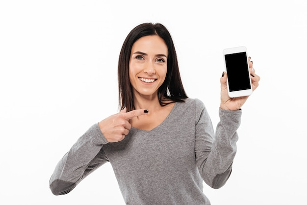 Frauenstellung lokalisiert, anzeige des handys zeigend.